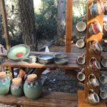 a picture of cups on a rack and pottery layed out from Sunrise pottery